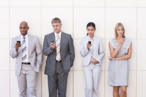 Business colleagues reading an SMS while in a line